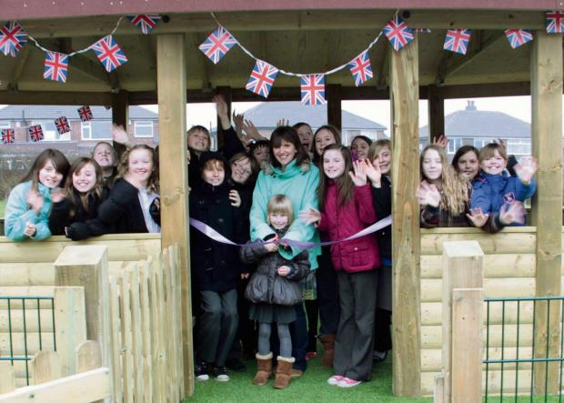 SUBMITTED PIC Caption:  Children at Otley All Saints C of E Primary celebrate, with former PTA chairman Sara Quin and Year 3 pupil Holly Homes cutting the ribbon, the opening of two new playground shelters. (7755691)