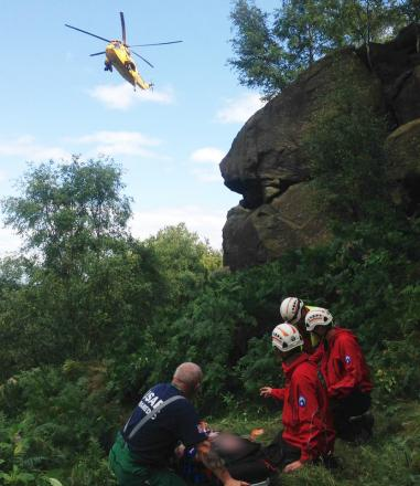Rescuers wait for a helicopter evacuation with the injured climber on Otley Chevin.