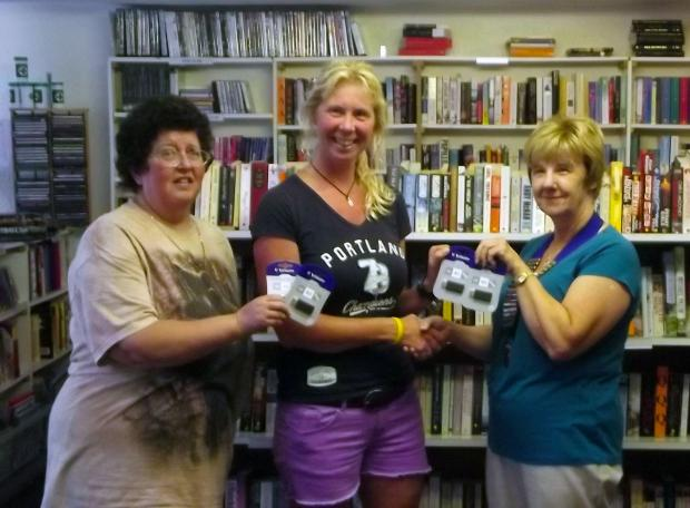 Tina, centre, is presented with the flash drives by Lion President Barbara Taylor and Lion Mary Ratcliffe
