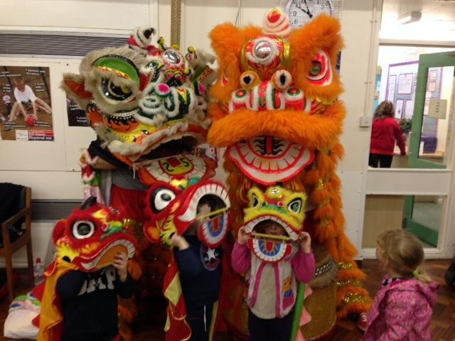 Performers and children in Chinese lion costumes at Otley's Little Green Frog Nursery.