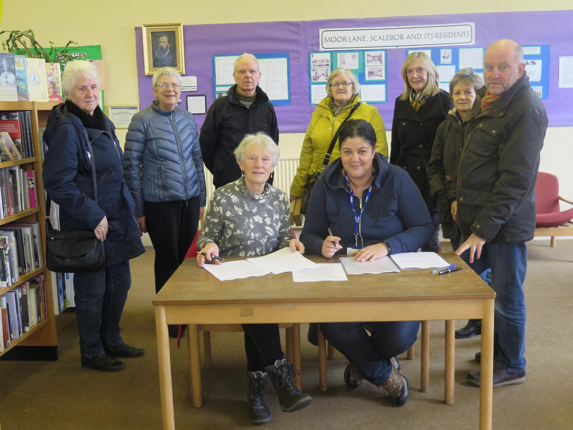 Parish Councillor Janet Souyave and Mandy Webb, Bradford Branch Libraries Manger, supported by some of the Burley Library volunteers sign the Service Level Agreement ensuring Burley Library will remain open after April 1, 2017