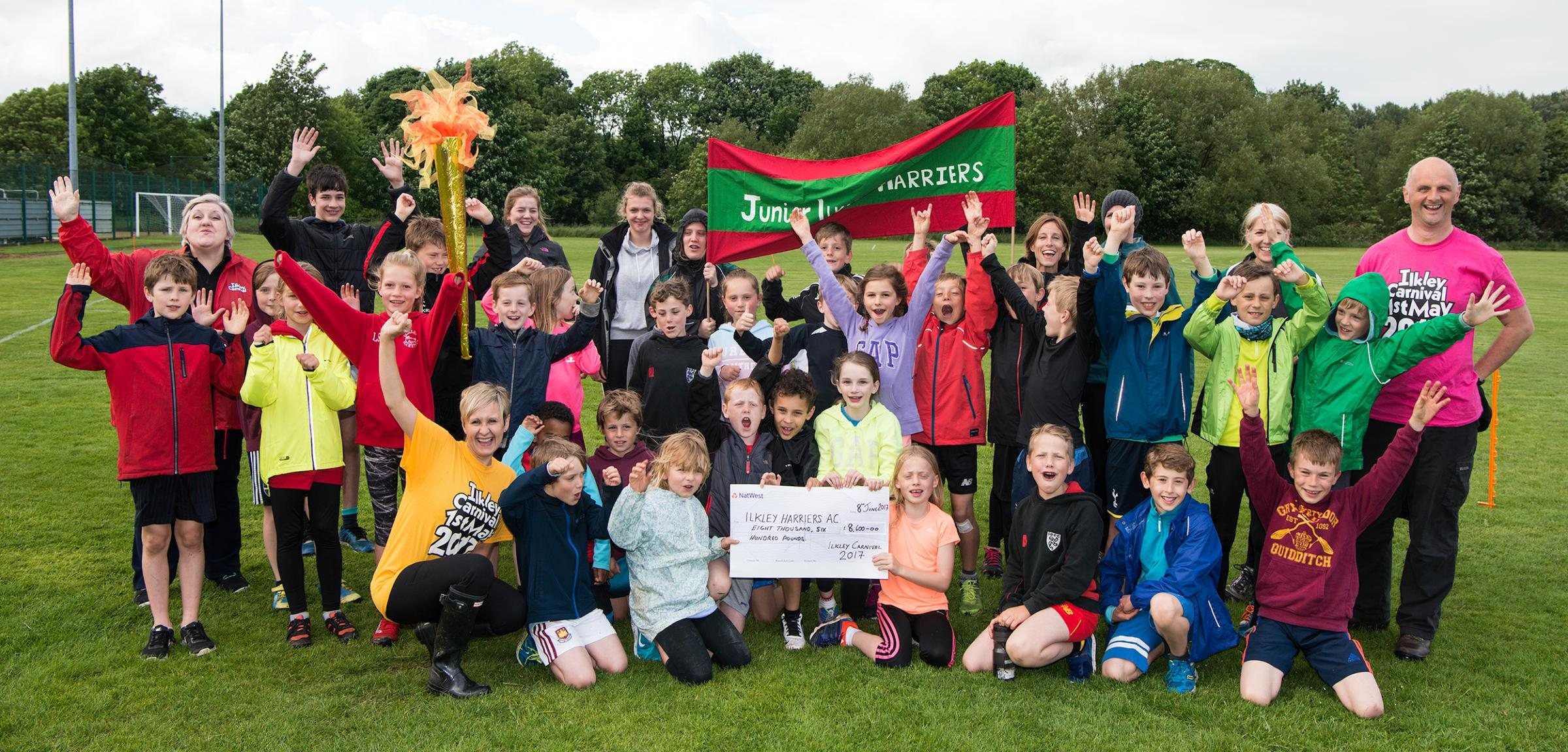 Jubilant members of 2017's primary beneficiary group, Ilkley Junior Harriers, as Ilkley Carnival committee members presented the £8,500 cheque