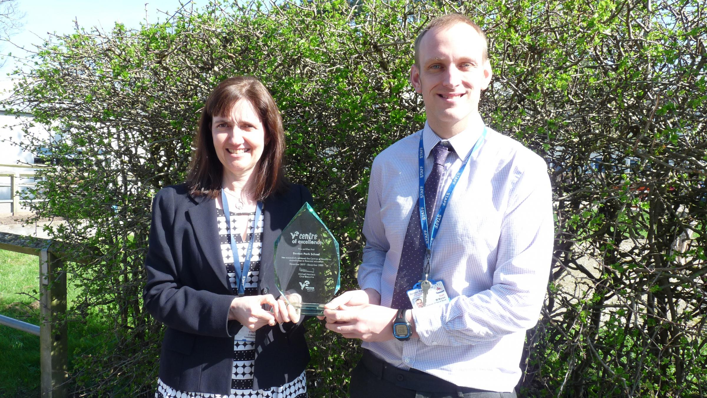 Headteacher Delia Martin and Matthew Marsh, Director of Social Studies and Business Champion, with the Centre of Excellence trophy
