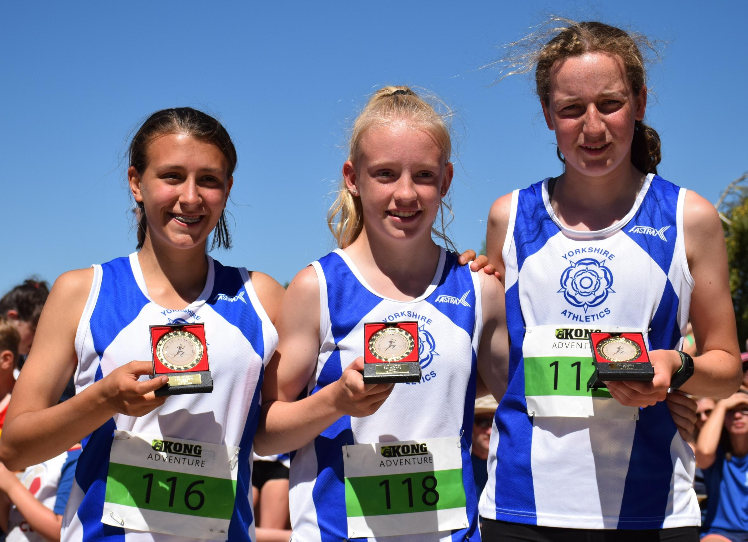 From left, Ilkley Harriers' Bernadette Raven, Lilli Carr and Emily Jones celebrate after winning gold in the girls' under-17s category at the Junior Inter-County Fell Running Championships. Picture: Dave Woodhead