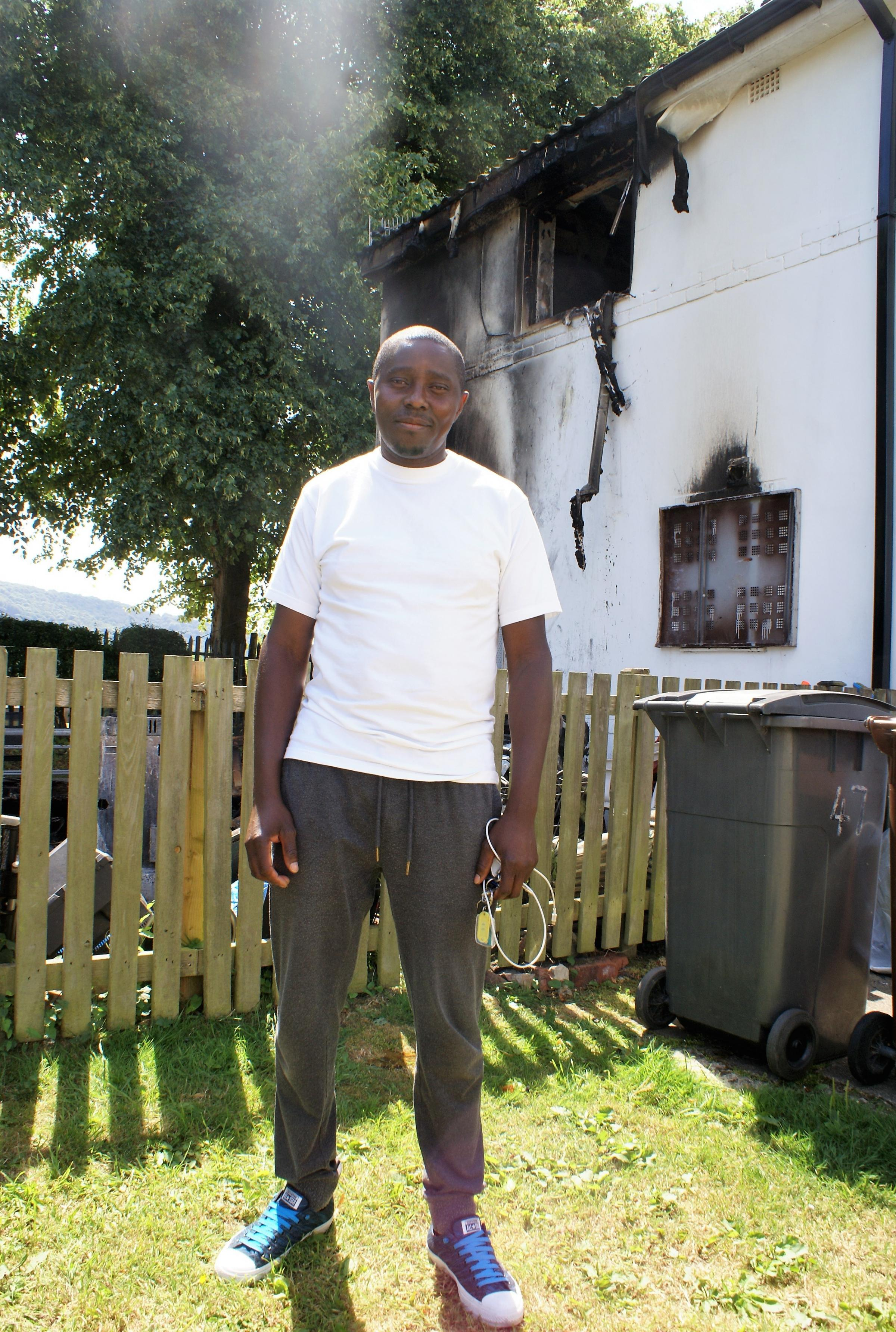 Olivier Masekessabou beside his neighbour's burnt-out house on The Crossways, Otley