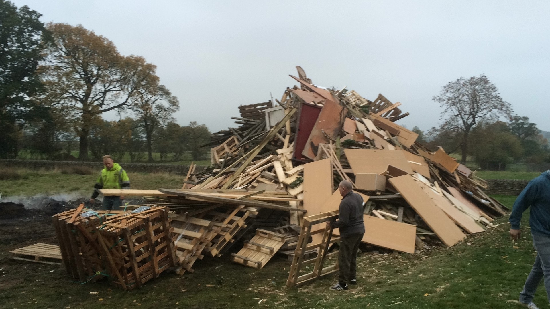 Workmen and residents helping to build a new bonfire for The Roebuck pub, near Otley, after vandals struck