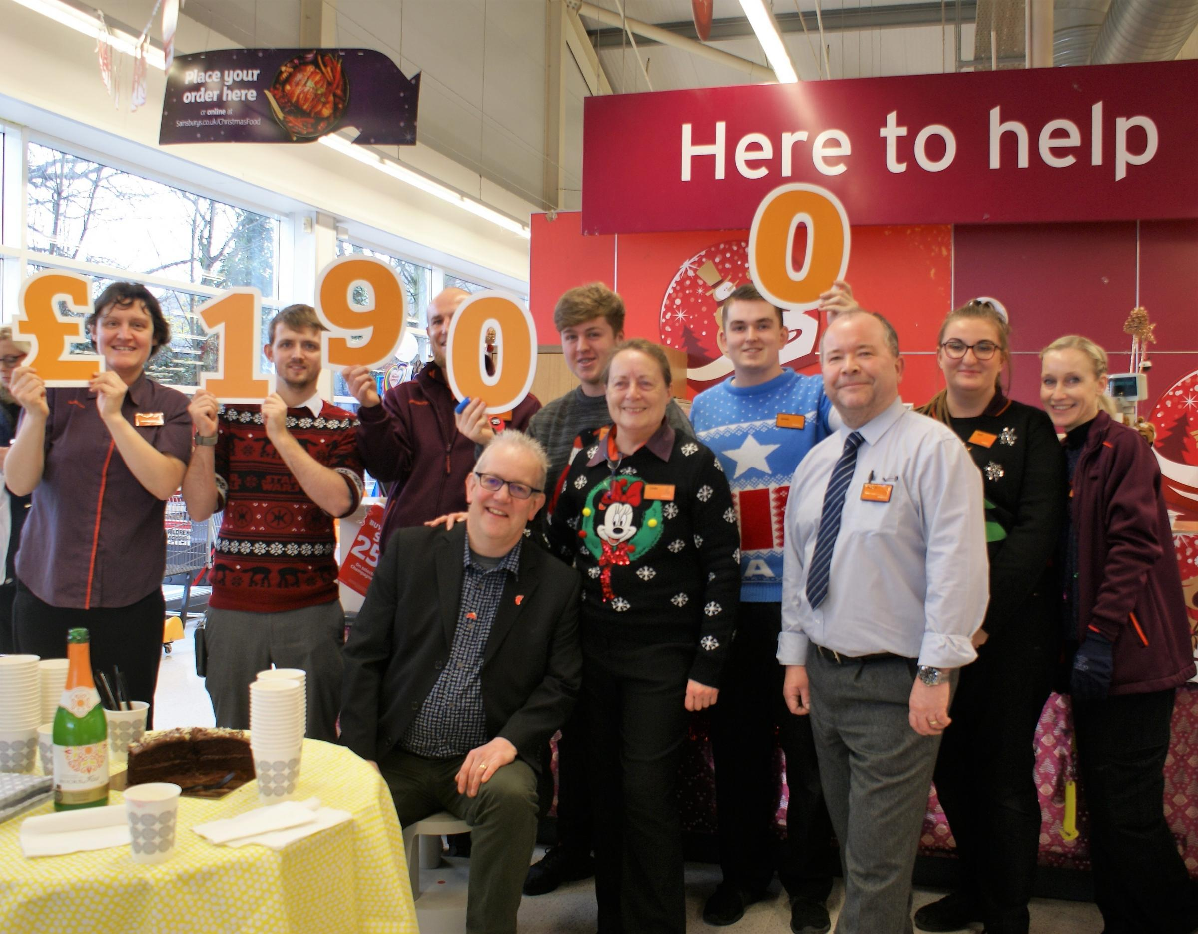 Sainsbury's Otley staff presenting £1,900 to Elliot's Footprint founder John Kerslake (seated)