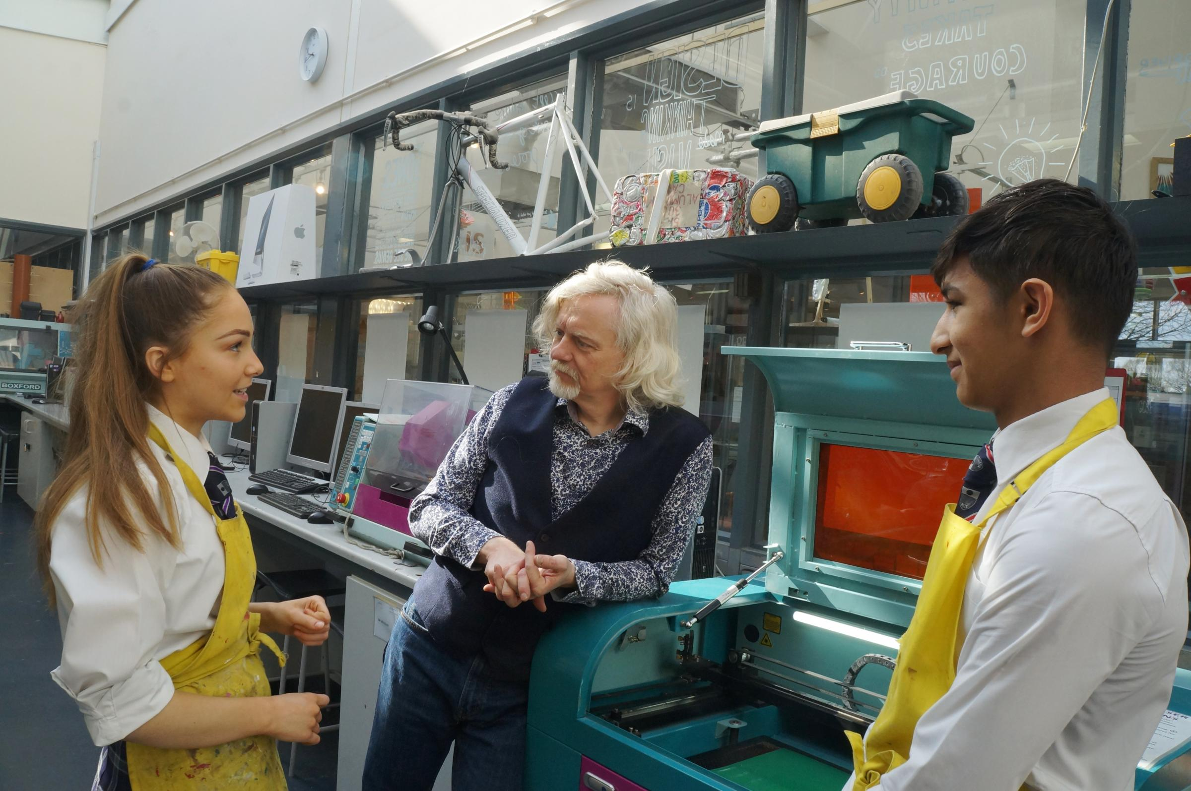 Year 10 students Zuzu Borland (left) and Faris Khan (right) show Marty Jopson the laser cutter during his visit to the design technology workshop at GSAL